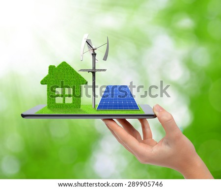 Hand holding tablet with green house, wind turbine and solar panel. Ecology concept. - stock photo