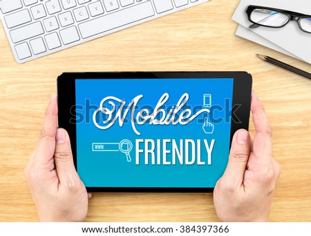 Hand holding tablet with Mobile friendly word on wood table ,Digital marketing concept - stock photo