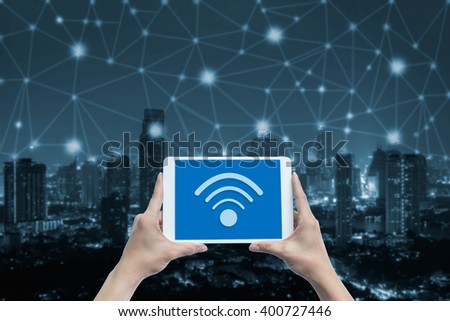 hand holding tablet with wifi icon on blue tone city scape and network connection concept  - stock photo