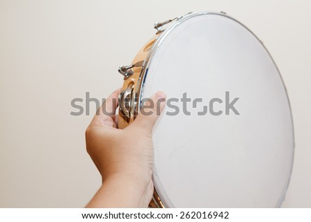 Hand holding tamborine with top white face showing - stock photo