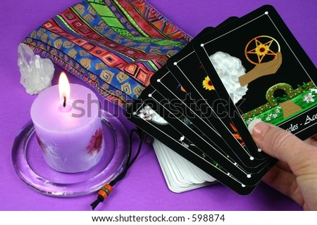 Hand holding tarot cards with deck and candle in background