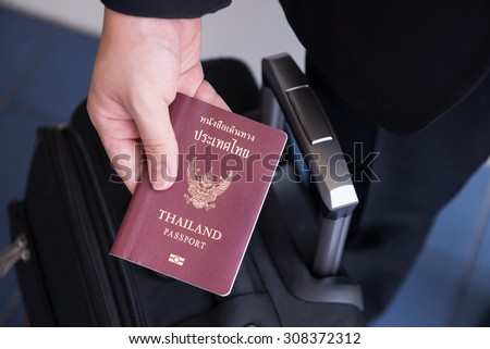 Hand holding Thai passport, ready to travel