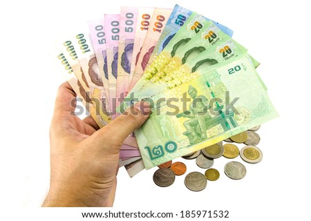 hand holding thailand banknotes and coins isolated on white