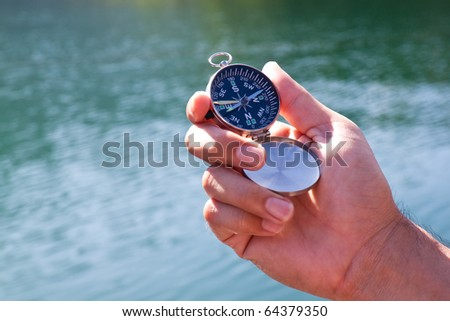 Hand holding the black compass - stock photo