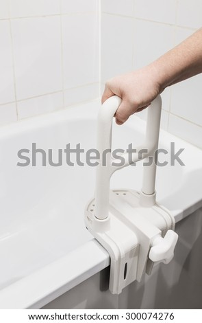 hand holding the handrail in the bathroom. Focus on the handrail - stock photo