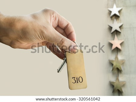 hand holding the key of the  luxury hotel suite - stock photo