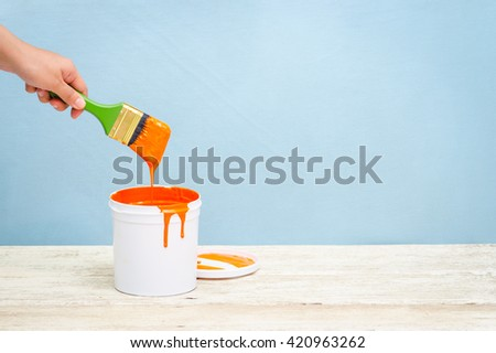 Hand holding the paint brush and White plastic bucket with orange color on wood,vintage background
