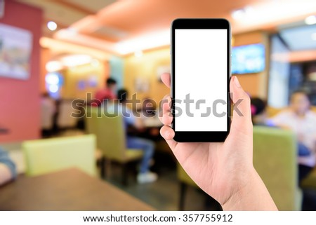 hand holding the phone tablet on blur restaurant background,Transactions by smartphone concept - stock photo
