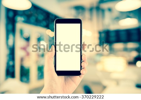 hand holding the phone tablet on blurred in shop or restaurant background;Transactions by smartphone concept - stock photo