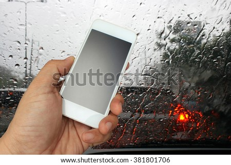 hand holding the smartphone on road view through car window with rain drops, Driving in rain. - stock photo