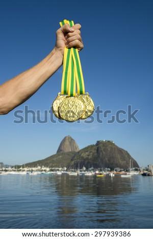 Hand holding three gold medals at Botafogo Beach Rio de Janeiro Brazil skyline - stock photo