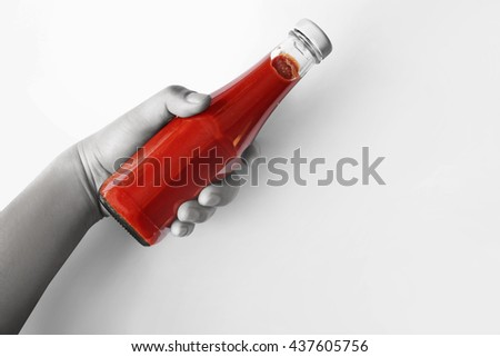 Hand holding Tomato ketchup bottle. Isolated on white background