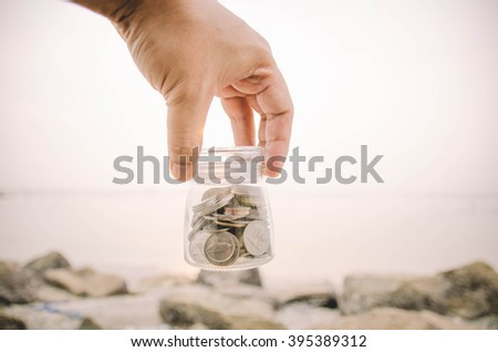 hand holding top of glass jar contain with coin concept.blur background at the beach during sunset - stock photo