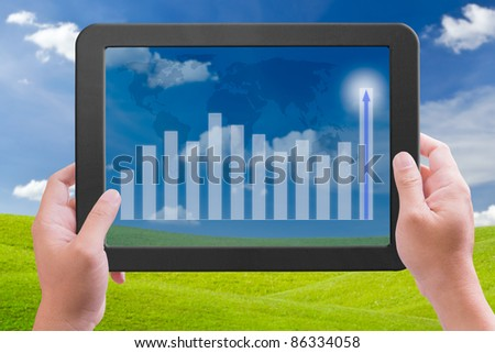 hand holding touch pad pc with higher graph - stock photo