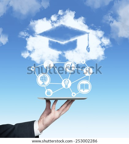 hand holding touch pad with graduation cap and education symbol - stock photo