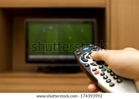 Hand holding TV remote control with a television football. - stock photo