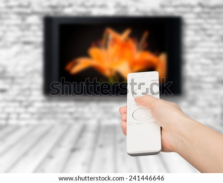 Hand holding TV remote control with a television in the background. Close up. - stock photo