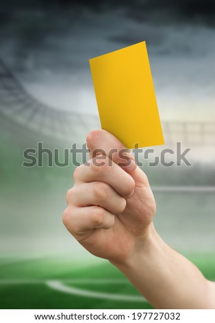 Hand holding up yellow card against football pitch in large stadium - stock photo