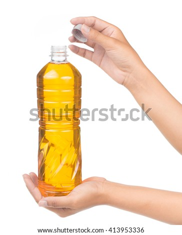 Hand holding Vegetable oil for cooking in a bottle isolated on white background - stock photo