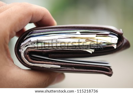 Hand holding very thick wallet selective focus on foreground - stock photo