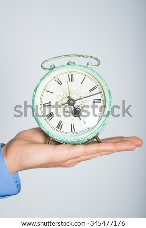 Hand holding vintage alarm clock. advertising or business concept, isolated on a gray background. - stock photo