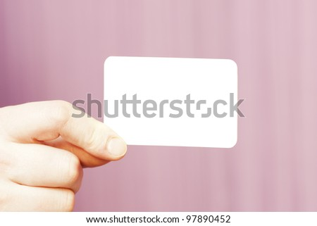 hand holding white business card on pink background - stock photo