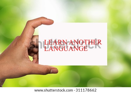 hand holding white card written learn another language over blur background - stock photo