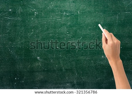 Hand holding white chalk and starting to write on blank chalkboard - stock photo