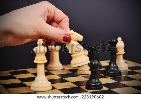 hand holding white chess knight on chessboard - stock photo