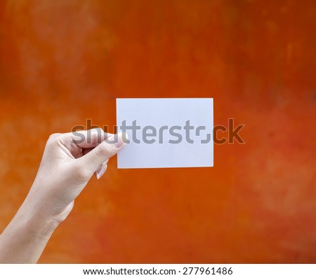 Hand holding white empty card with space on orange wall - stock photo