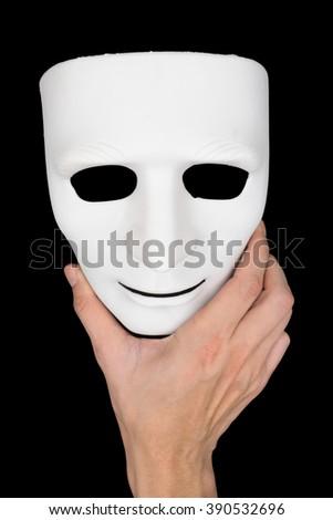 Hand holding white mask on black background. - stock photo