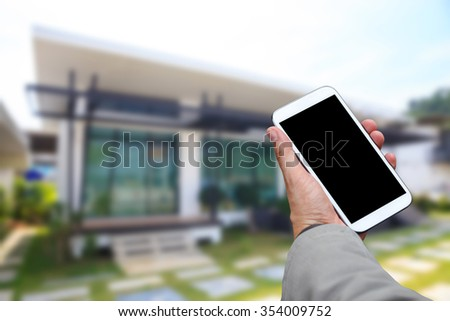 Hand holding white mobile smart phone over blurred house background. - stock photo