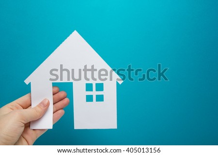 Hand holding white paper house figure on blue background. Real Estate Concept. Ecological building. Copy space top view - stock photo
