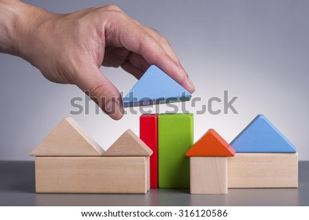 Hand holding wooden house (Housing Loan Concept) - stock photo