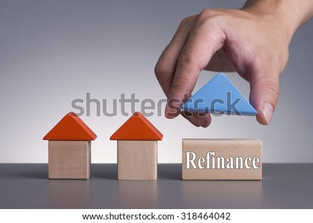 Hand holding wooden house (Housing Loan Concept) with word Refinance - stock photo