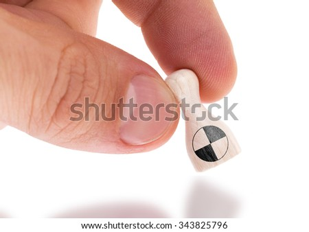 Hand holding wooden pawn with a flag painting, selective focus, Crash test dummy - stock photo