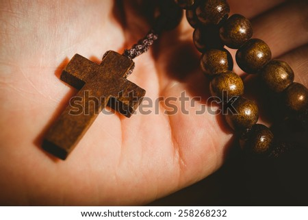 Hand holding wooden rosary beads in close up - stock photo