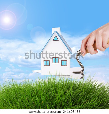 Hand holding wooden toy house on field background - stock photo