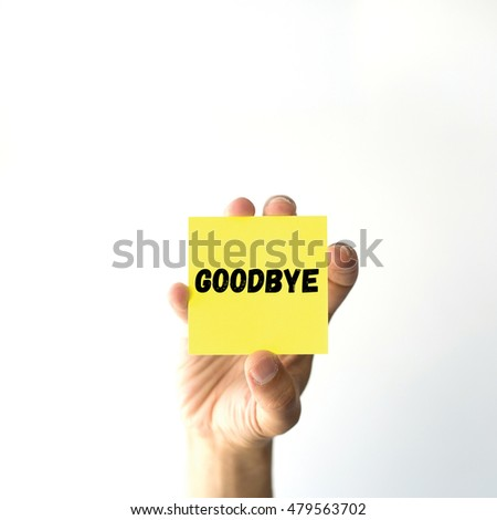 Hand holding yellow sticky note written GOODBYE