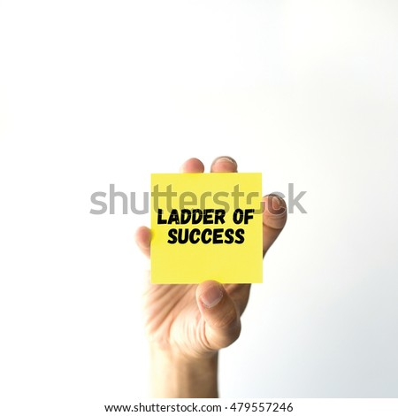 Hand holding yellow sticky note written LADDER OF SUCCESS