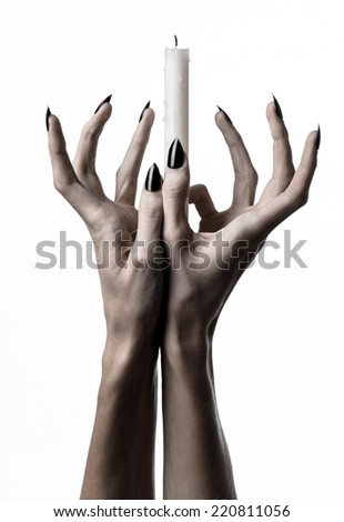 Hand holds a candle witches, black nails, lit candle, hand witches, the devil's hand, halloween theme, white background, hand in wax, ritual, solitude, horror, monster, hands of Death, isolated - stock photo
