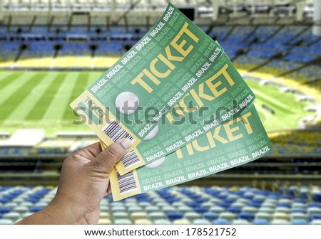 Hand holds a homemade soccer tickets on an empty stadium - stock photo