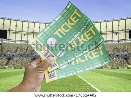 Hand holds a homemade soccer tickets on the stadium - stock photo