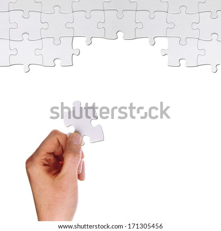 hand holds a part of a puzzles to solve it - stock photo