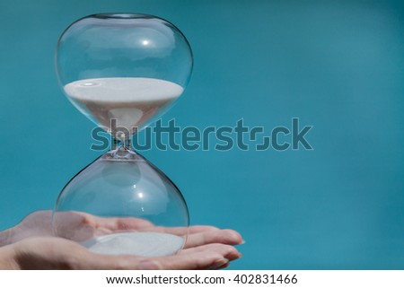 Hand holds an hourglass on green background. Concept for business deadline and leadership. Blue Ocean Strategy