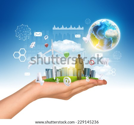 Hand holds city of skyscrapers on green grass and businessman walking forward. Earth and fying letters near hand. Element of this image furnished by NASA - stock photo