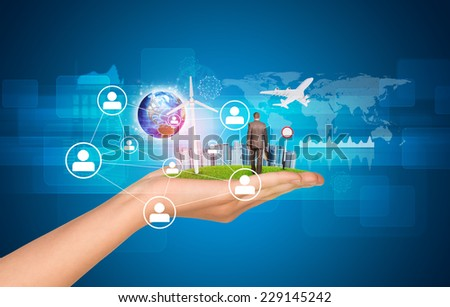 Hand holds city of skyscrapers on green grass and businessman walking forward. Earth and network with people icons near hand. Element of this image furnished by NASA - stock photo