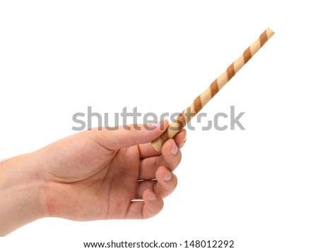 Hand holds striped chocolate wafer rolls
