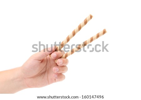 Hand holds striped chocolate wafer rolls. Isolated on a white background.