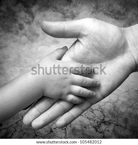 hand holds the hand of his father's son - stock photo